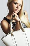 Moderne schöne blonde Frau mit mit Handtasche. Einkauf Stockfotografie