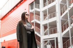Moderne schöne junge attraktive Frau mit stilvoller Sonnenbrille im modischen grünen Mantel mit der grauen Strickjacke, die in de stockfoto