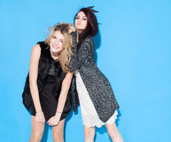 Moderne schöne junge Freundinnen, die zusammen nahe einem blauen Hintergrund stehen Brunettehaar verdreht Blondine Lustiges und P Lizenzfreies Stockfoto