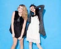 Moderne schöne junge Freundinnen, die zusammen nahe einem blauen Hintergrund stehen Lustiges haben und Aufstellung Betrachten der Stockfotos