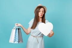 Moderne Schönheit des Porträts im Sommerkleid, Strohhut, der Pakettaschen mit Käufen nach dem Einkauf hält stockbild