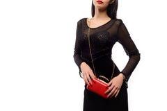 Moderne Schönheitsfrau mit einer roten Tasche und schwarzen einem Abendkleid Stockbilder