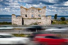 Moderne schnelle Autos und eine alte Ruine Lizenzfreies Stockfoto