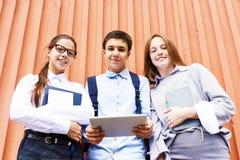 Moderne Schoolkinderen die bij Camera in openlucht glimlachen stock foto