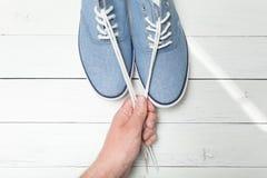 Moderne Schuhe auf einem hellen hölzernen Hintergrund, weiße Spitzee in einer Hand stockbild