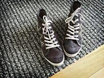 Moderne Schuhe auf grauem gestreiftem Teppich Stockbilder