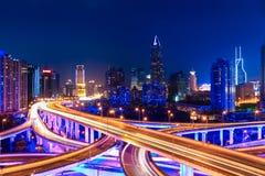 Moderne stadshorizon met uitwisselingsviaduct bij nacht Royalty-vrije Stock Afbeeldingen