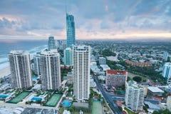 Moderne Stadt an der Dämmerung mit Ozean dazu Stockbild