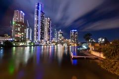 Moderne Stadt nachts mit beweglichen Wolken Lizenzfreie Stockfotos