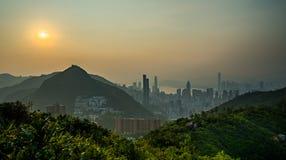 Moderne Stadt nahe bei Berg im Sonnenuntergang Stockfotografie