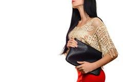 Moderne stilvolle junge Frau im roten Rock mit schwarzer Kupplung Stockfotografie