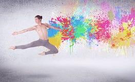 Moderne straatdanser die met kleurrijke verfplonsen springen Stock Foto