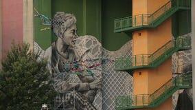 Moderne straatkunst in het maken, reusachtige graffiti van vrouw op de muur onder brug stock videobeelden