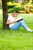 Moderne studentenzitting in park onder de boom en de lezing BO royalty-vrije stock foto