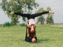 Moderne Tätigkeit des gesunden Lebensstils Junge Paare, die acro Vogel-Yogahaltung tun Stockfotos
