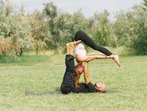 Moderne Tätigkeit des gesunden Lebensstils Junge Paare, die acro Vogel-Yogahaltung tun Stockbilder