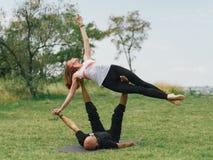 Moderne Tätigkeit des gesunden Lebensstils Junge Paare, die acro Vogel-Yogahaltung tun Lizenzfreie Stockfotos