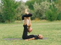 Moderne Tätigkeit des gesunden Lebensstils Junge Paare, die acro Vogel-Yogahaltung tun Lizenzfreie Stockbilder