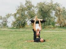 Moderne Tätigkeit des gesunden Lebensstils Junge Paare, die acro Vogel-Yogahaltung tun Stockfotografie