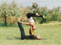 Moderne Tätigkeit des gesunden Lebensstils Junge Paare, die acro Vogel-Yogahaltung tun Stockbild