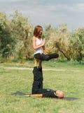 Moderne Tätigkeit des gesunden Lebensstils Junge Paare, die acro Vogel-Yogahaltung tun Stockfoto