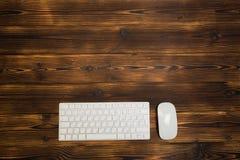 Moderne Tastatur auf dem Holztisch mit Maus im B?ro lizenzfreie stockfotografie