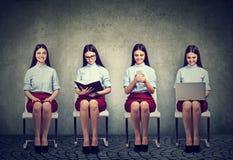 Moderne Technologie gegen traditionelle Informationsquellen Frauen mit Buch, Laptop und Handy Stockfoto