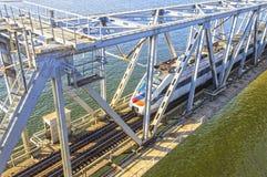 Moderne trein die over de brug over de rivier daveren stock foto