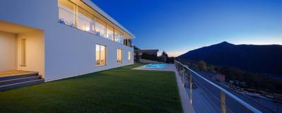 Moderne villa, buitenkant in de nacht, lichten  stock afbeeldingen