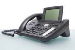 Moderne voiptelefoon op bureau Stock Afbeeldingen