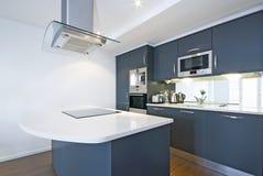 Moderne volledig gepaste keuken in wit en grijs stock afbeelding