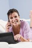 Moderne vrouw die op laag met telefoon, laptop wordt ontspannen stock afbeeldingen