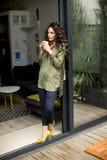 Moderne vrouw die zich naast een glas deur en het drinken koffie bevinden royalty-vrije stock afbeelding