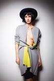Moderne vrouw met zwarte hoed op grijs Stock Foto's