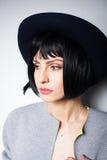 Moderne vrouw met zwarte hoed op grijs Stock Foto