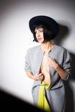 Moderne vrouw met zwarte hoed op grijs Stock Fotografie