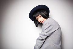 Moderne vrouw met zwarte hoed op grijs Royalty-vrije Stock Foto's