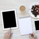 Moderne vrouwelijke werkruimte met vrouwelijke handen, smartphone, tablet, blocnote, bessen en latte over witte houten achtergron royalty-vrije stock fotografie
