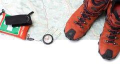 Moderne wandernde Schuhe und Kompaß auf Karte Lizenzfreies Stockbild