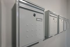 Moderne weiße metallische Postkästen für eine Wohnung in Folge gegen eine weiße gemalte Wand mit Zahlen auf ihnen und Verschlüsse lizenzfreie stockfotografie