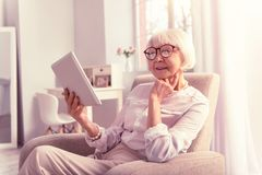 Moderne wijze gepensioneerde die door Internet-bankwezen betalen stock foto's