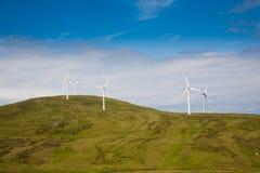 Moderne Windmühlen auf einem grünen Hügel Stockfoto