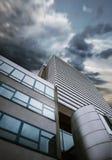Moderne wolkenkrabberzaken die stormachtige hemelachtergrond bouwen Royalty-vrije Stock Foto