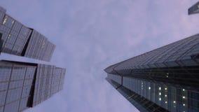 Moderne Wolkenkratzer der ungewöhnlichen Form, gemacht vom Glas Untere hohe Ansicht mit Rotation stock video