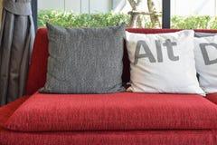 Moderne woonkamer met hoofdkussens op de rode bank en het decor Stock Afbeeldingen