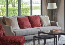 Moderne woonkamer met rode hoofdkussens op bank en dacorativ Royalty-vrije Stock Afbeeldingen
