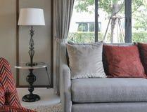 Moderne woonkamer met rode hoofdkussens op bank en decoratieve schemerlamp Royalty-vrije Stock Foto