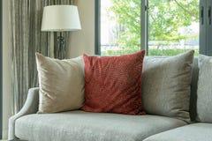 Moderne woonkamer met rode hoofdkussens op grijze bank en decoratieve lamp thuis Royalty-vrije Stock Foto's