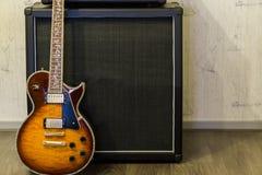 Moderne zonnestraal elektrische gitaar die zich voor versterker, de professionele achtergrond van het muziekmateriaal bevinden stock afbeelding