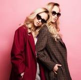 Moderne zwei blonde Frauen im Mantel mit Sonnenbrille Modeherbst-Winterfoto lizenzfreie stockbilder